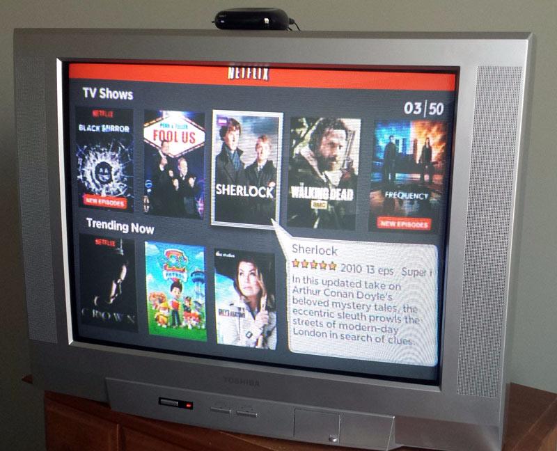 An old tube TV setup like a Smart TV with Netflix playing